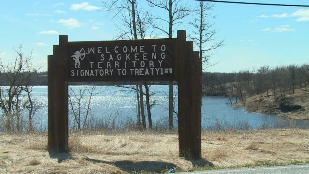 Une pancarte, positionnée devant un lac, marque l'entrée dans la Première Nation de Sagkeeng.