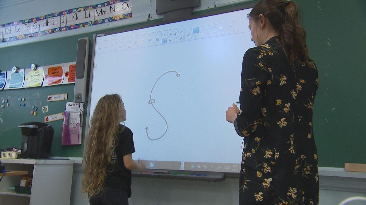 Une étudiante explique quelque chose à une élève.