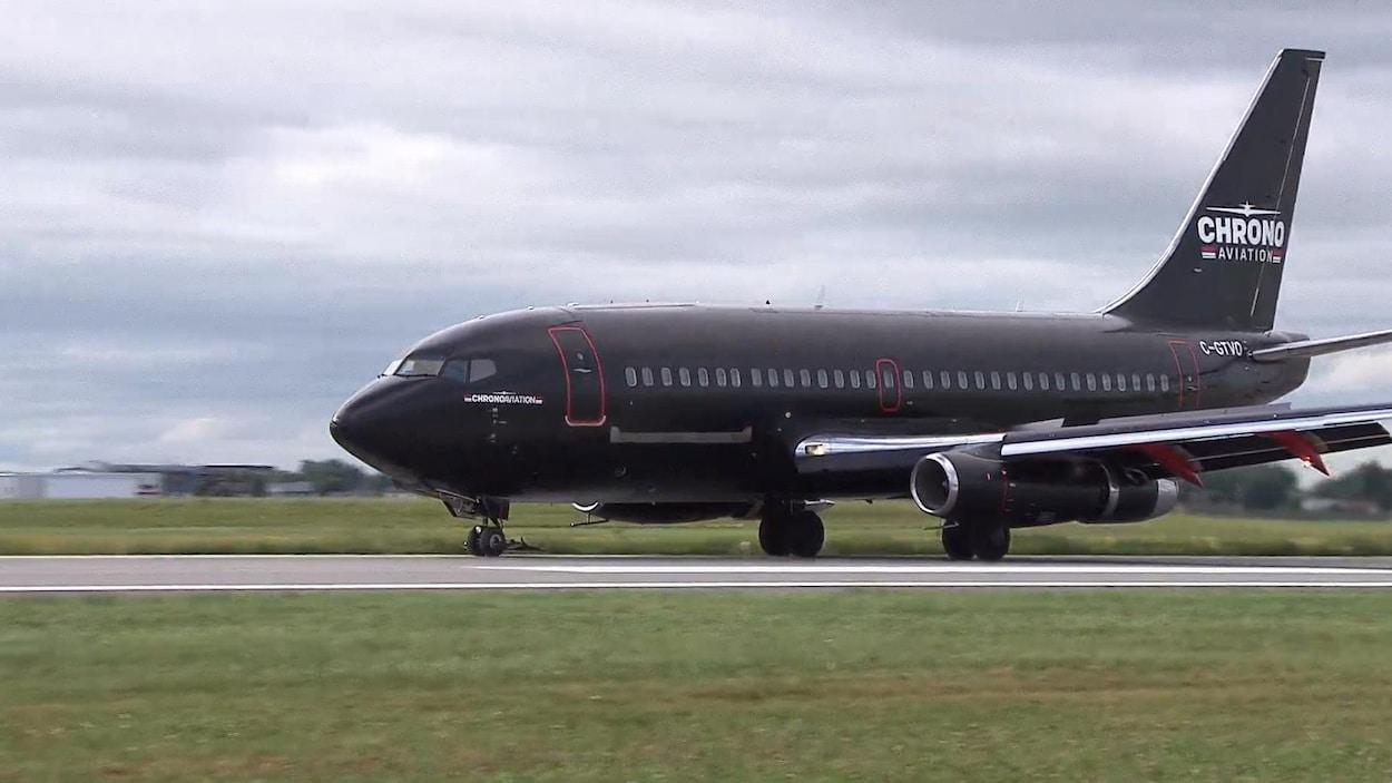 Un Boeing 737-200 de couleur noire roule sur la piste principale de l'aéroport de Saint-Hubert.