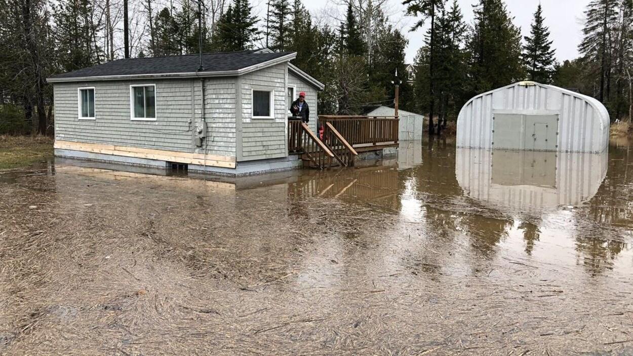 L'homme debout sur un patio regarde l'eau et les débris qui entourent sa maison