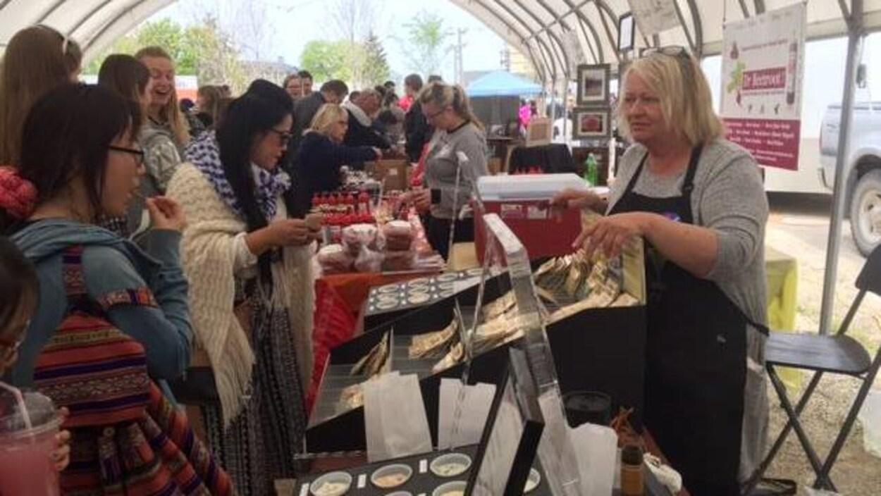 Des étals de produits artisanaux sont présentés devant un public qui goûte des spécialités.