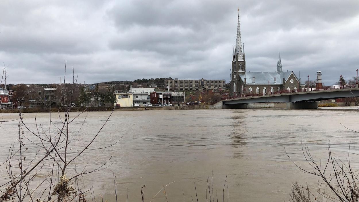 Le centre-ville de Sainte-Marie apparaît sous un ciel menaçant, alors que la rivière Chaudière atteint un niveau inquiétant près de l'église situé au coeur de la municipalité.
