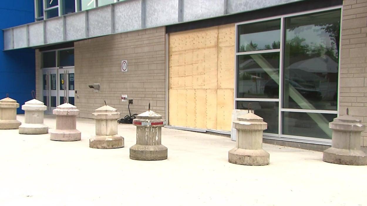 Des bornes en béton devant une façade réparée au contreplaqué.