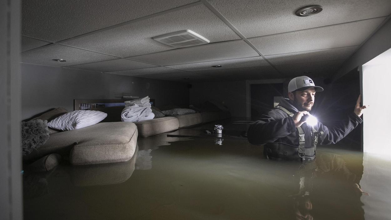 Un homme avec une lampe de poche dans son sous-sol inondé. Il a de l'eau plus haut que la taille.