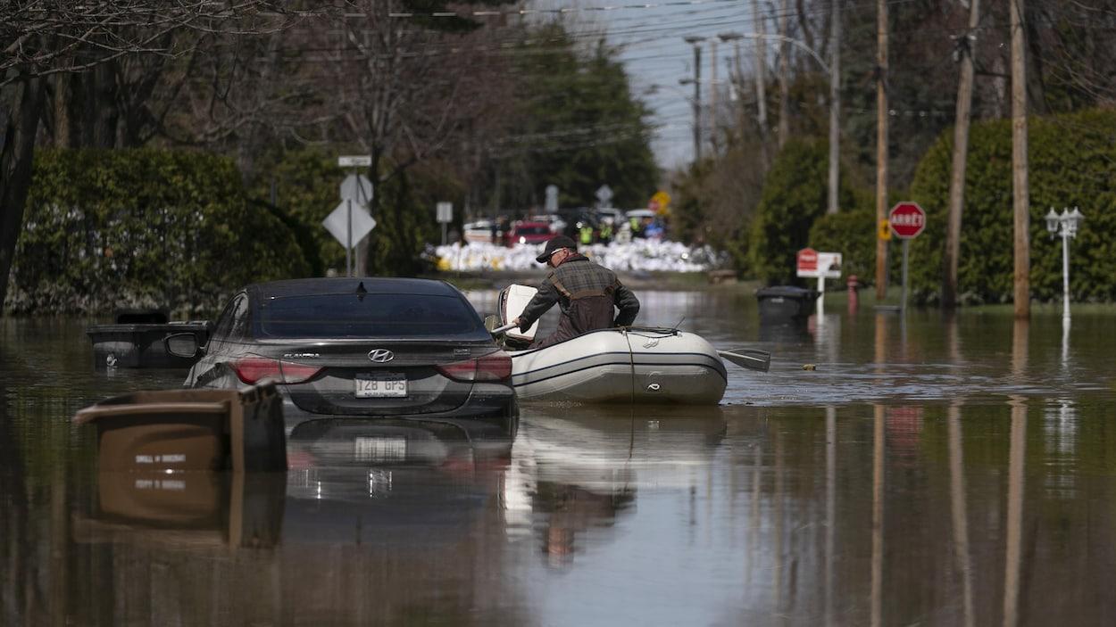 Un homme à bord d'une embarcation rame à côté d'une voiture à moitié immergée.