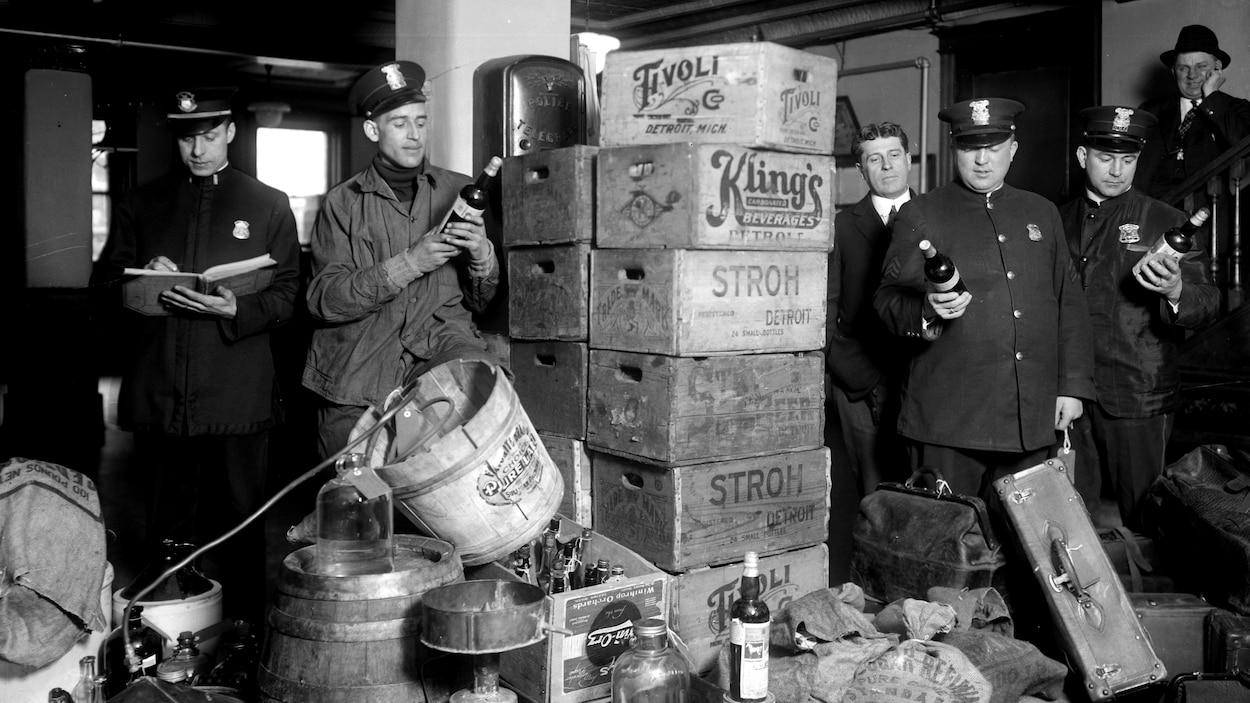 Des policiers tiennent des bouteilles d'alcool de contrebande.