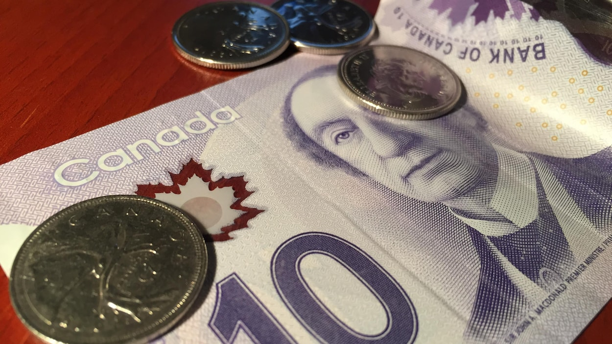 Une somme de onze dollars repose sur une table.