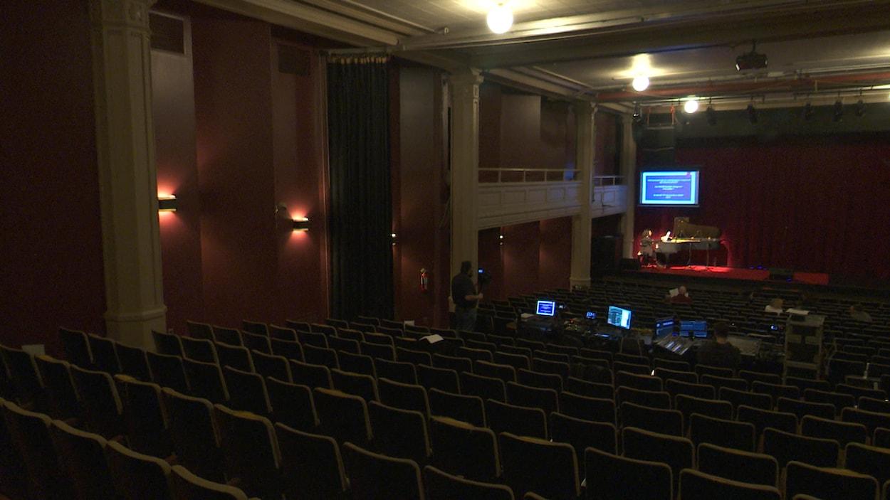 Intérieur de la salle André-Gagnon vide, alors qu'un pianiste pratique sur scène.