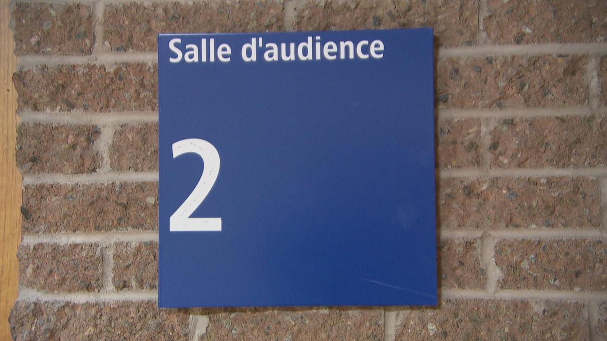 Une affiche indique la présence de la salle d'audience 2.