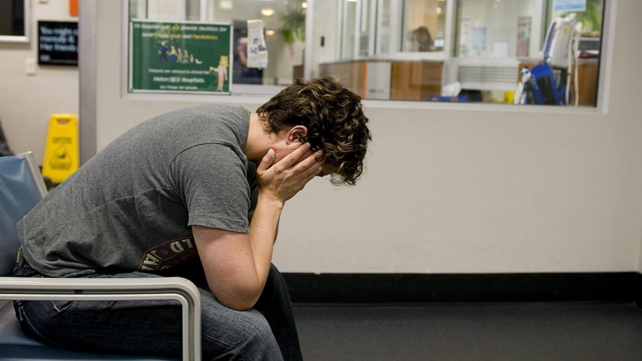 Un homme attend dans une salle d'attente à l'urgence.