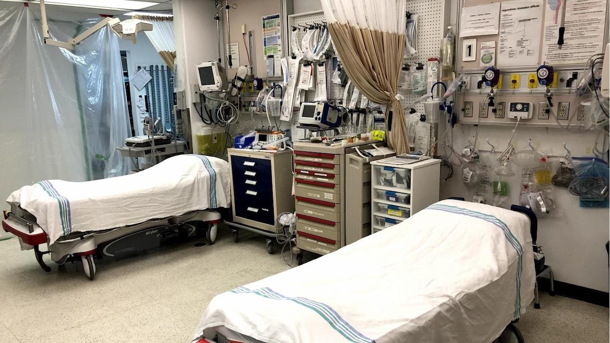 Deux lits entourés de matériel médical de soins intensifs dans une salle.