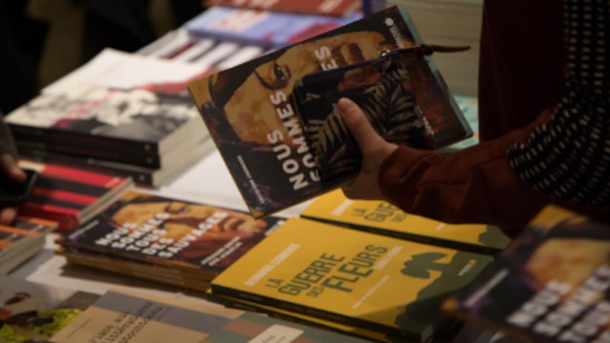 Des livres posés sur une table, et une main qui tient un livre.
