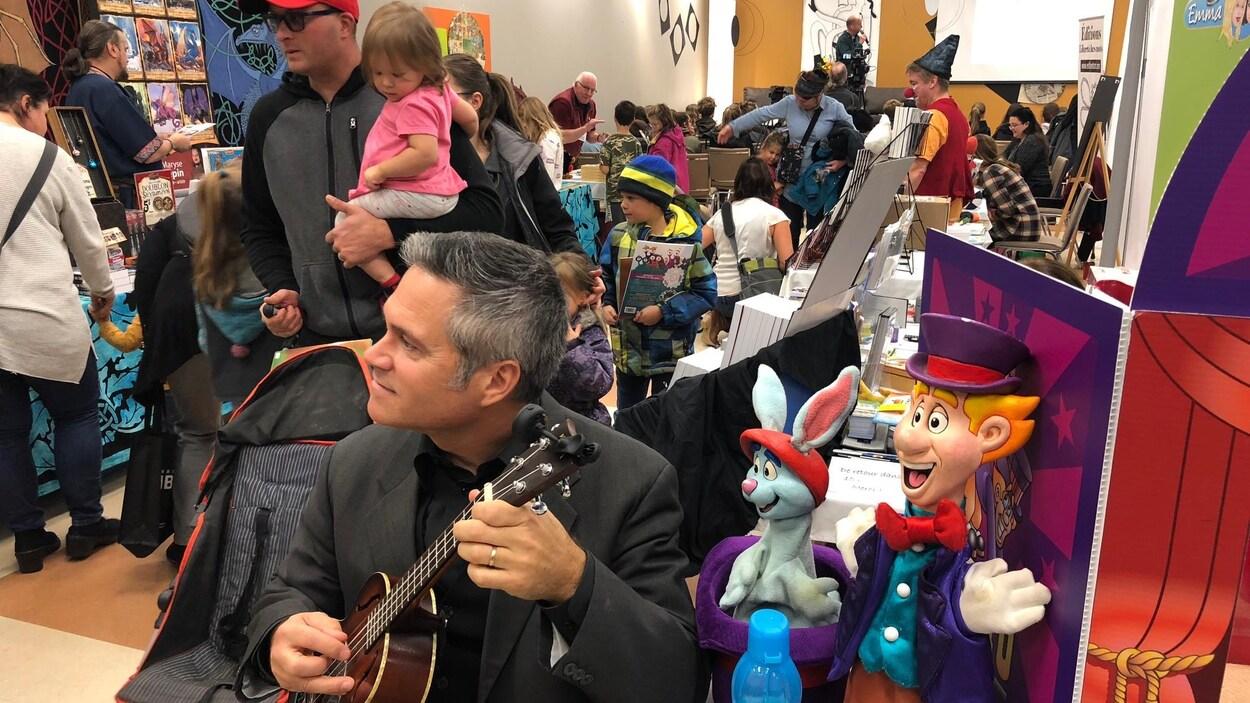 Un homme assis joue de la guitare. Derrière lui, des dizaines de parents et d'enfants se déplacent entre les kiosques de livres.