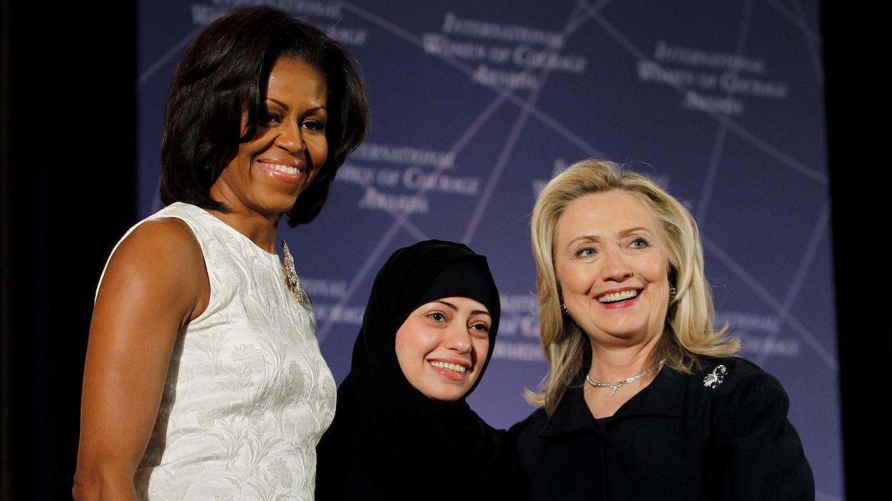 Trois femmes, dont l'une portant un hijab, sourient sur une scène.