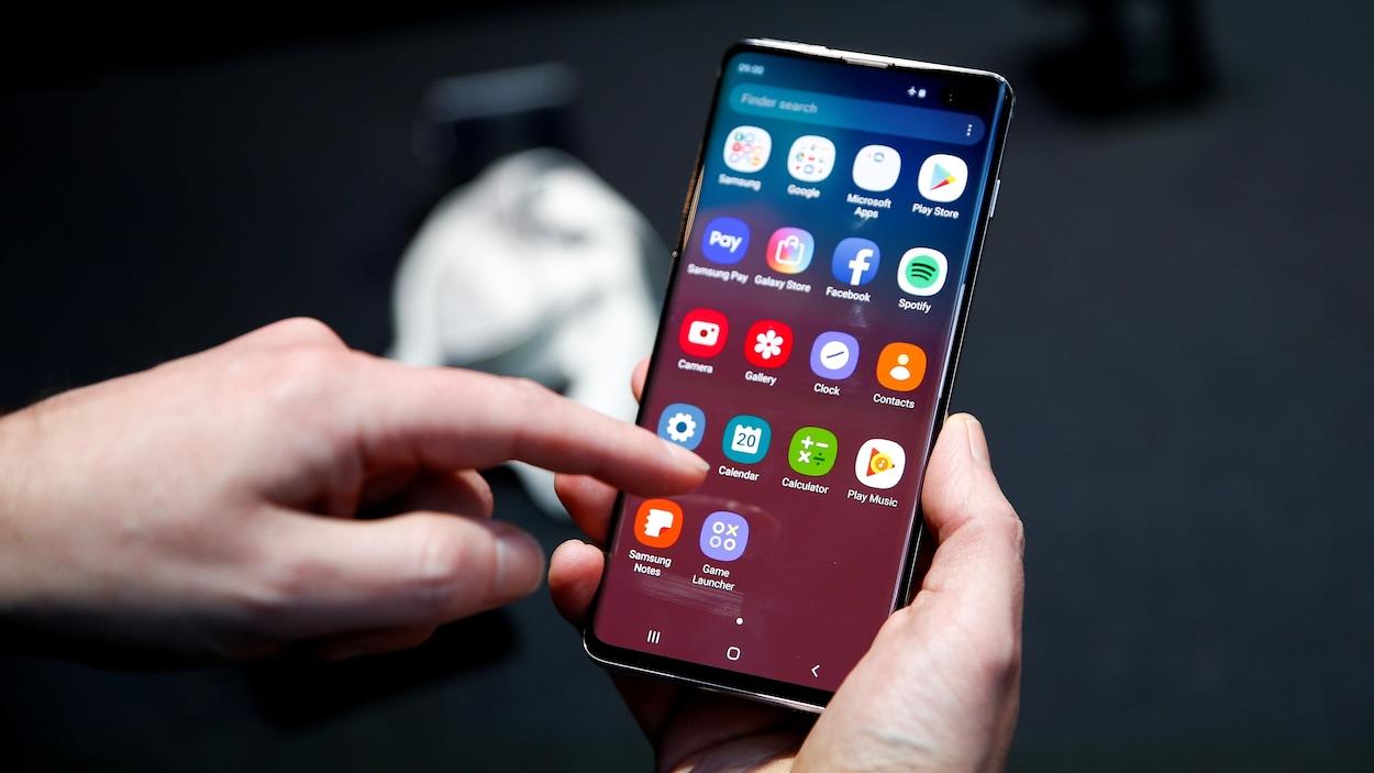 Une personne tient d'une main un téléphone intelligent Samsung Galaxy S10 et pose un doigt sur l'écran de son autre main.