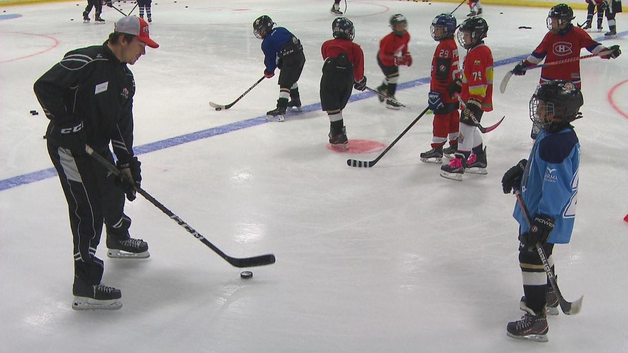 Samuel Girard sur la glaces avec de jeunes hockeyeurs.