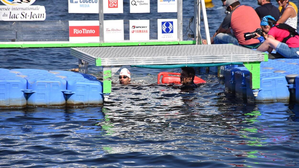 Un nageur arrive à proximité d'un quai.