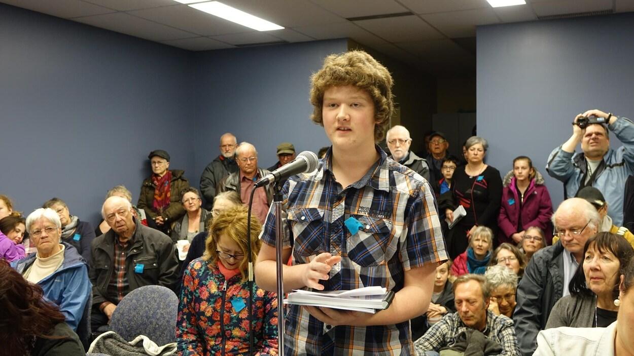 Jeune de 15 ans avec le document dans les mains, parlant au micro
