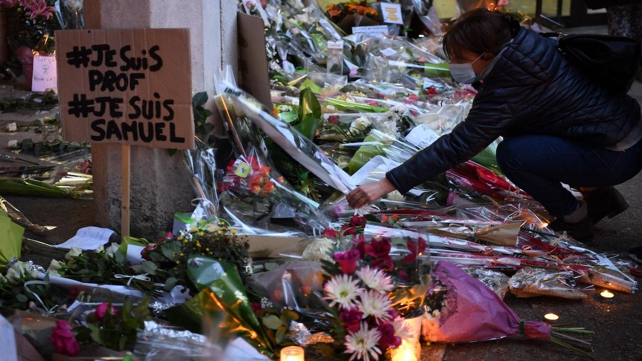 Une femme dépose une gerbe de fleurs au milieu de dizaines d'autres.