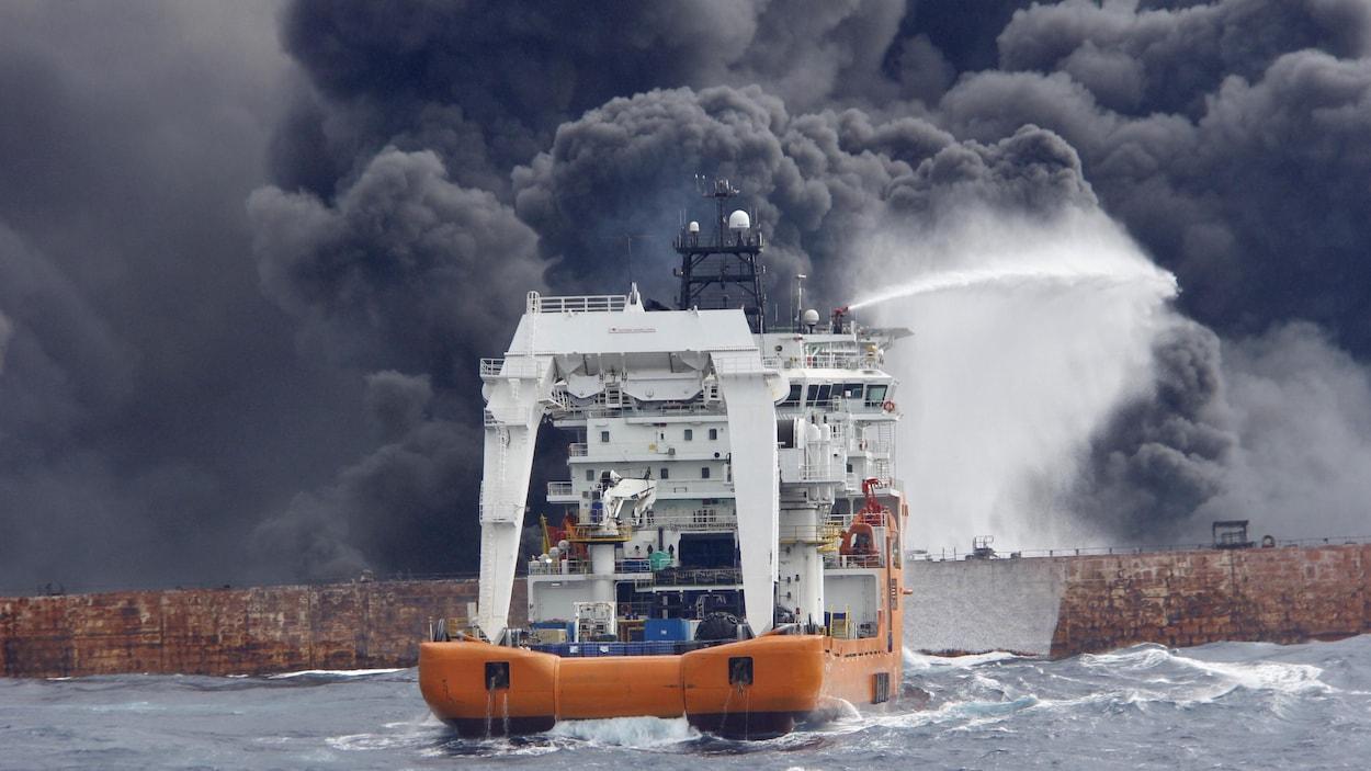 Une équipe de secours tente d'éteindre le feu qui consume lentement le pétrolier iranien Sanchi, au large des côtes chinoises, avant que le navire ne sombre en pleine mer.