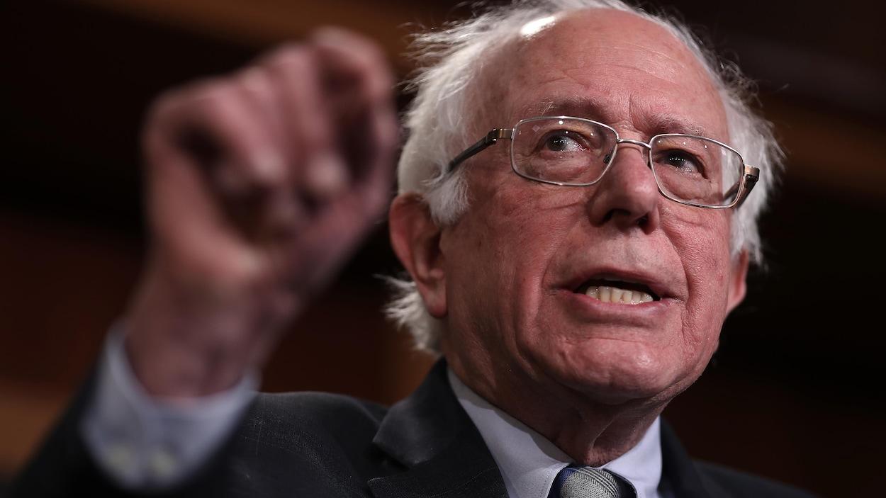 Bernie Sanders, le bras levé, s'adresse aux journalistes.