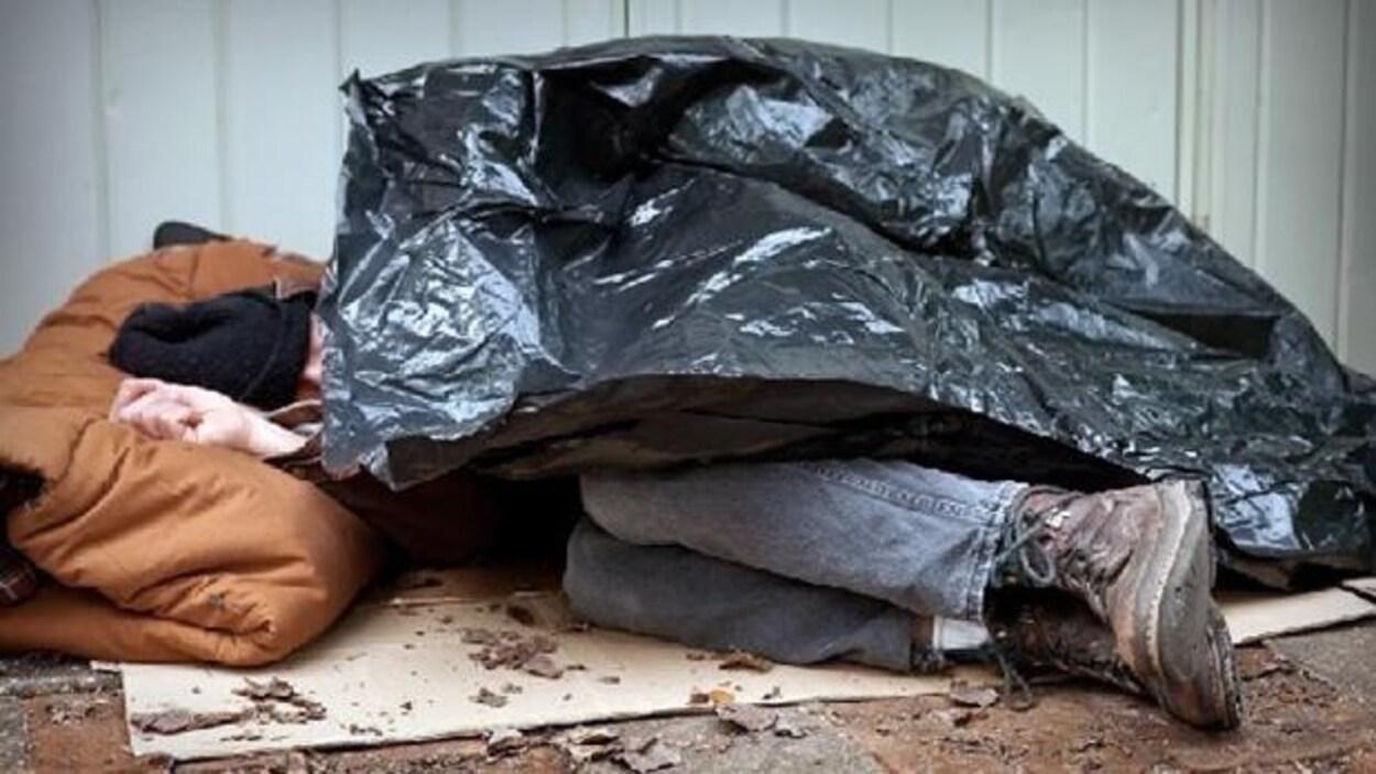 Un sans-abri dort à l'extérieur sur un carton, un sac de poubelle en guise de couverture.