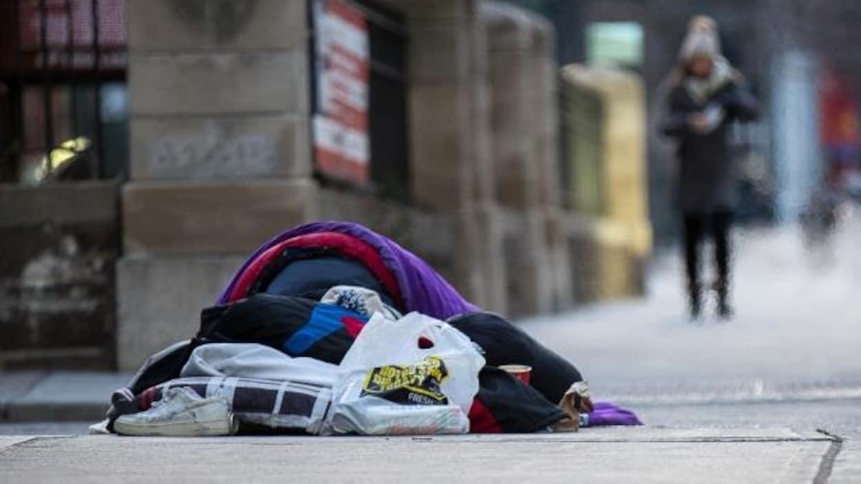Un sans-abri dort sur le trottoir.