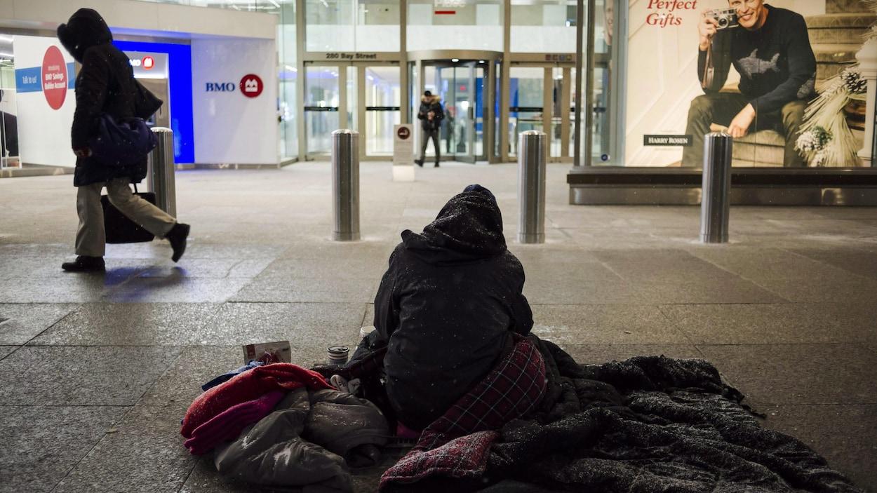 Un sans-abri sur le trottoir l'hiver à Toronto.