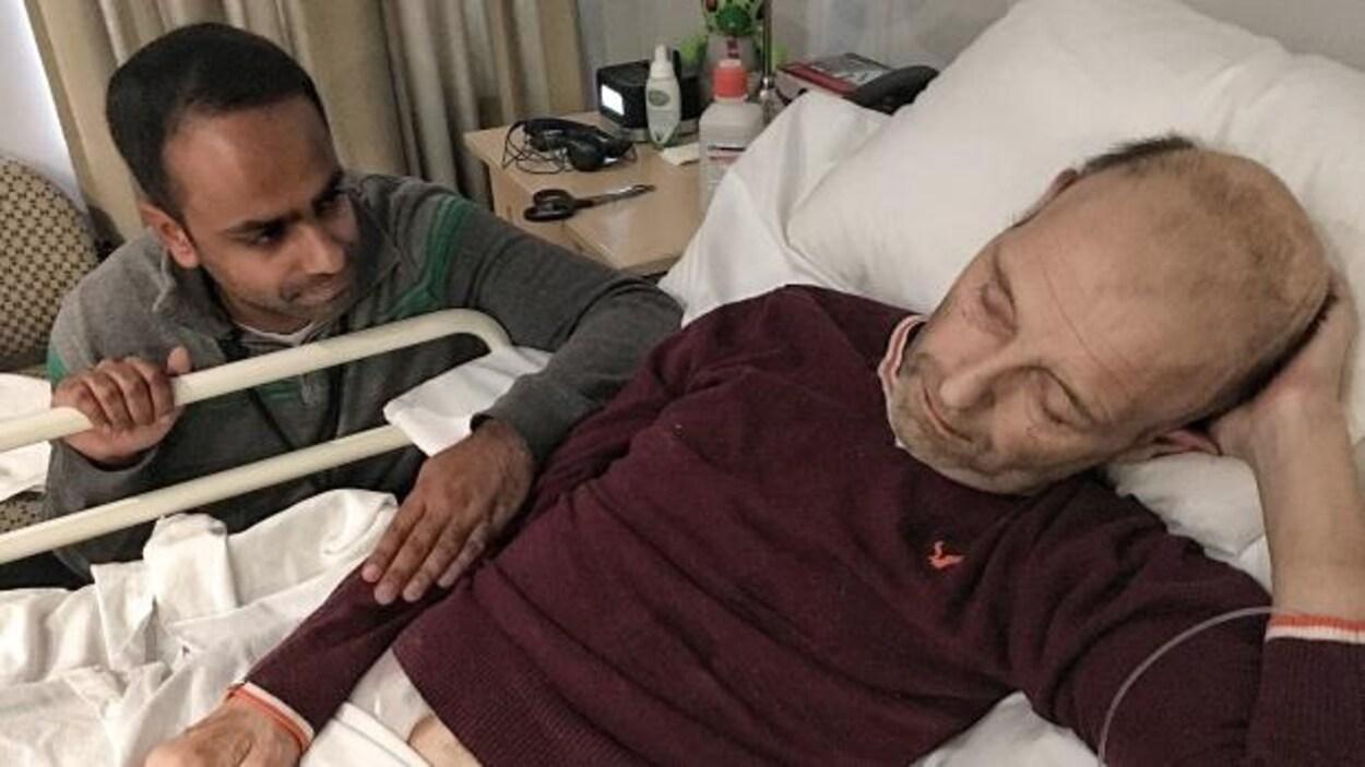 Le Dr Naheed Dosani aux côtés d'un sans-abri étendu sur un lit.