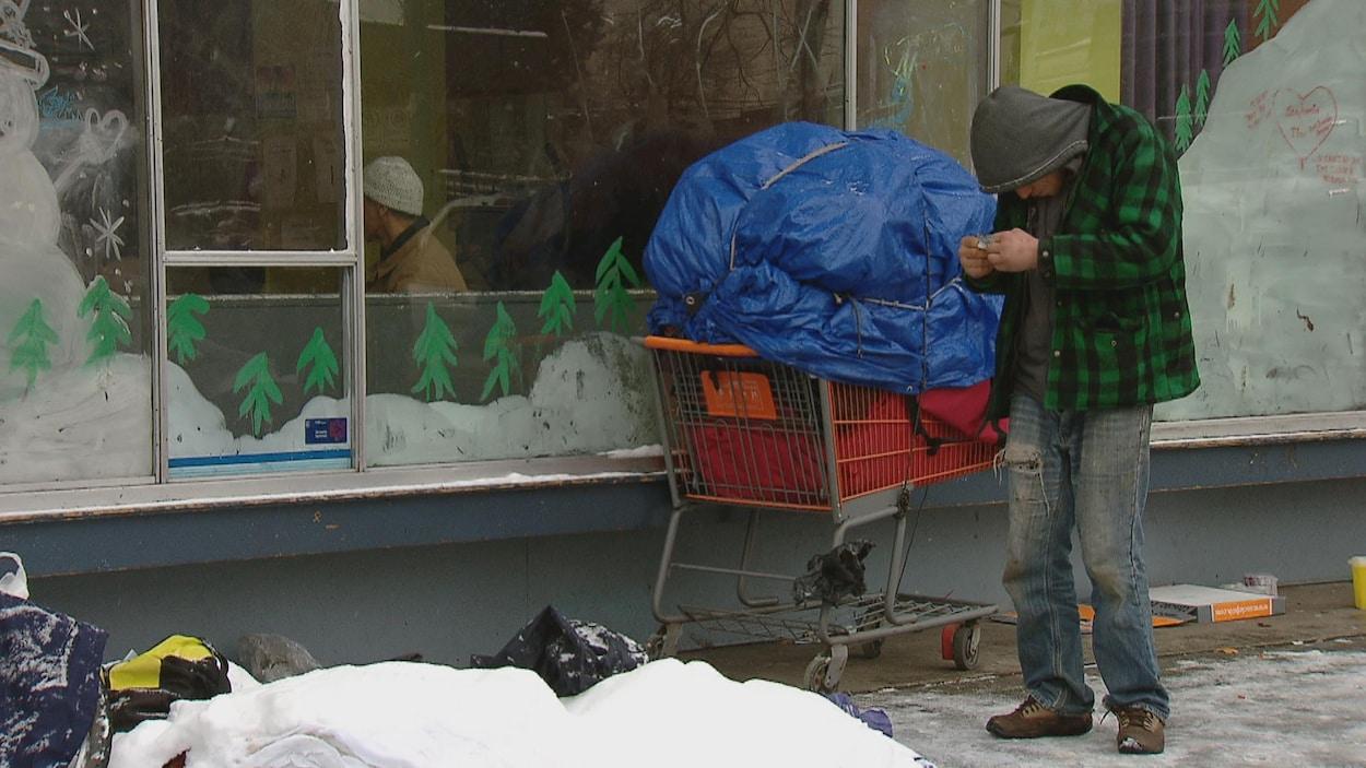 Un itinérant est devant un centre d'hébergement. Il est penché et tient un papier dans ses mains. Il est entouré de neige et d'un panier d'épicerie rempli couvert d'une toile bleue pour protéger ses effets personnels.