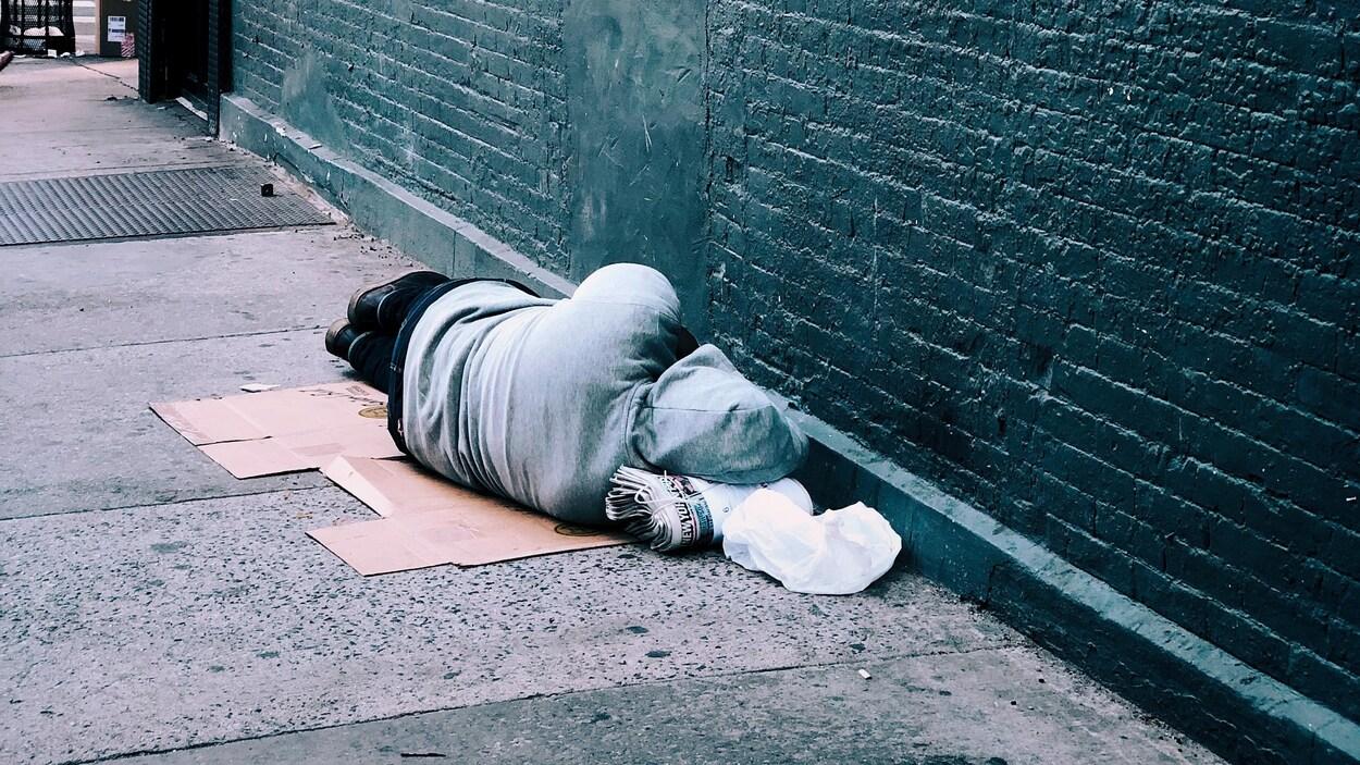 Un homme est allongé sur le trottoir, sur un morceau de carton le long d'un mur.