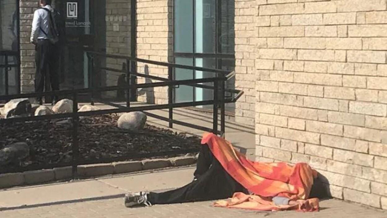 Un homme qui dort dans une rue près du refuge Lighthouse.