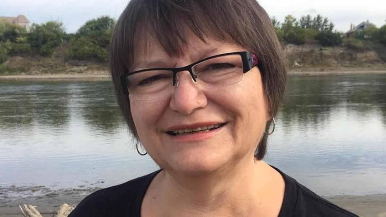 Une femme portant des lunettes et des créoles devant un plan d'eau.