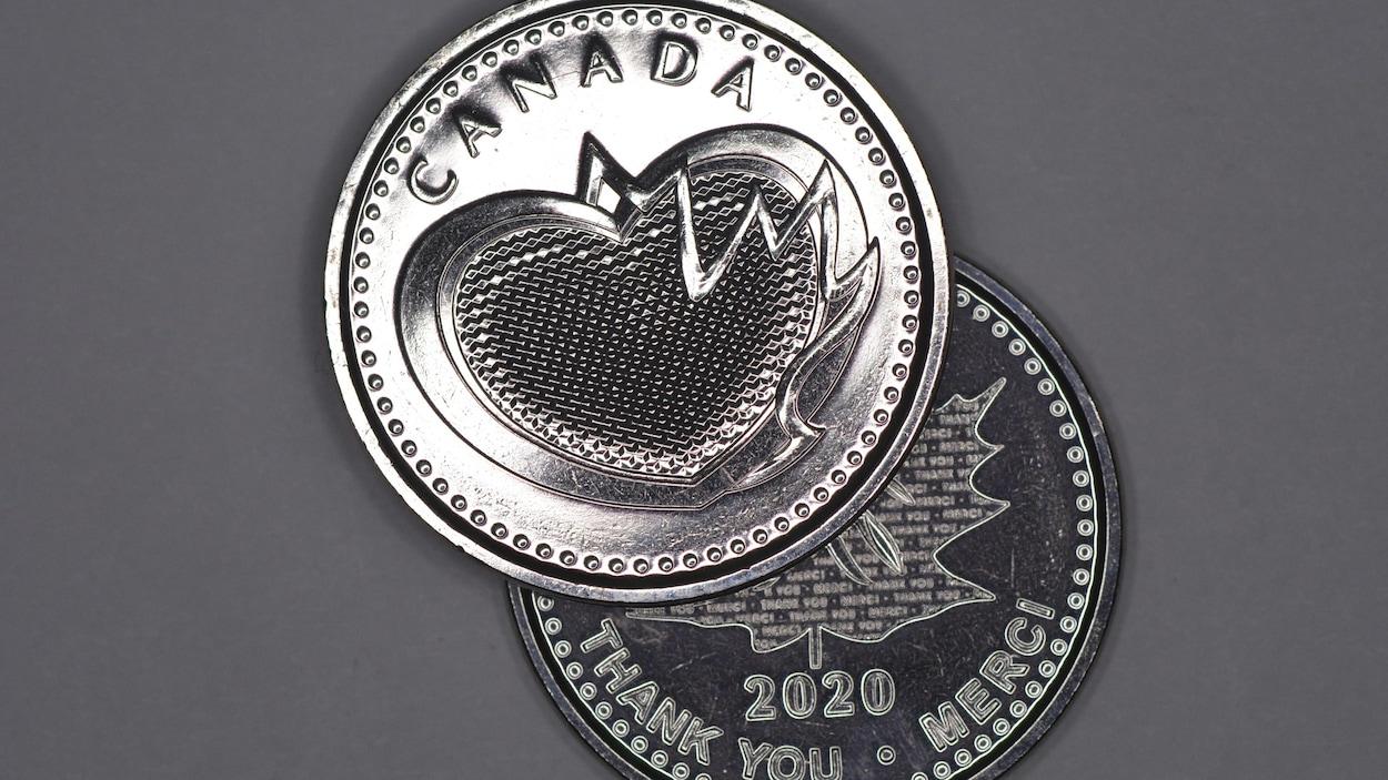 Une médaille en acier sur lequel on voit un coeur et la feuille d'érable.