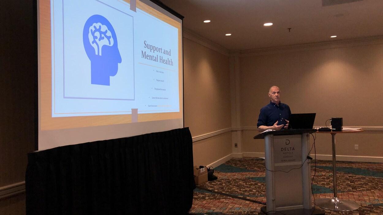 Un dessin d'une tête est projeté sur un écran. Doug Ellis, est à sa droite, il discute de santé mentale.