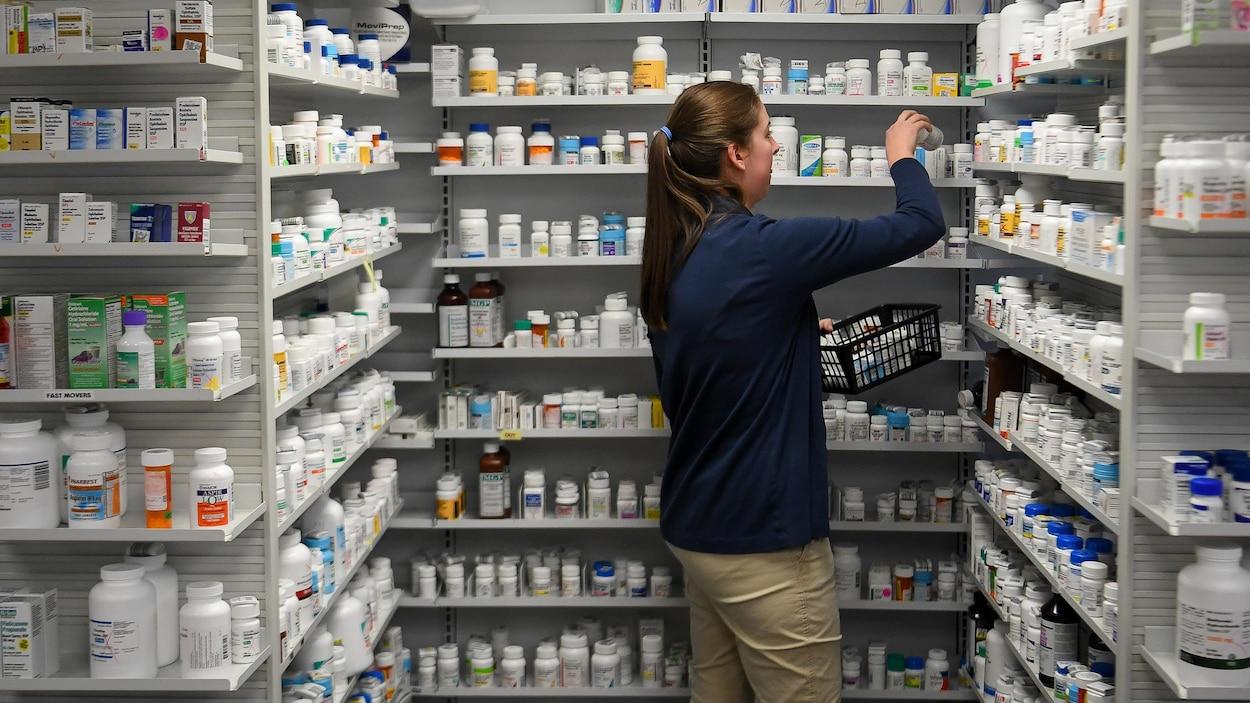 Une employée d'une pharmacie dépose des médicaments sur des tablettes.