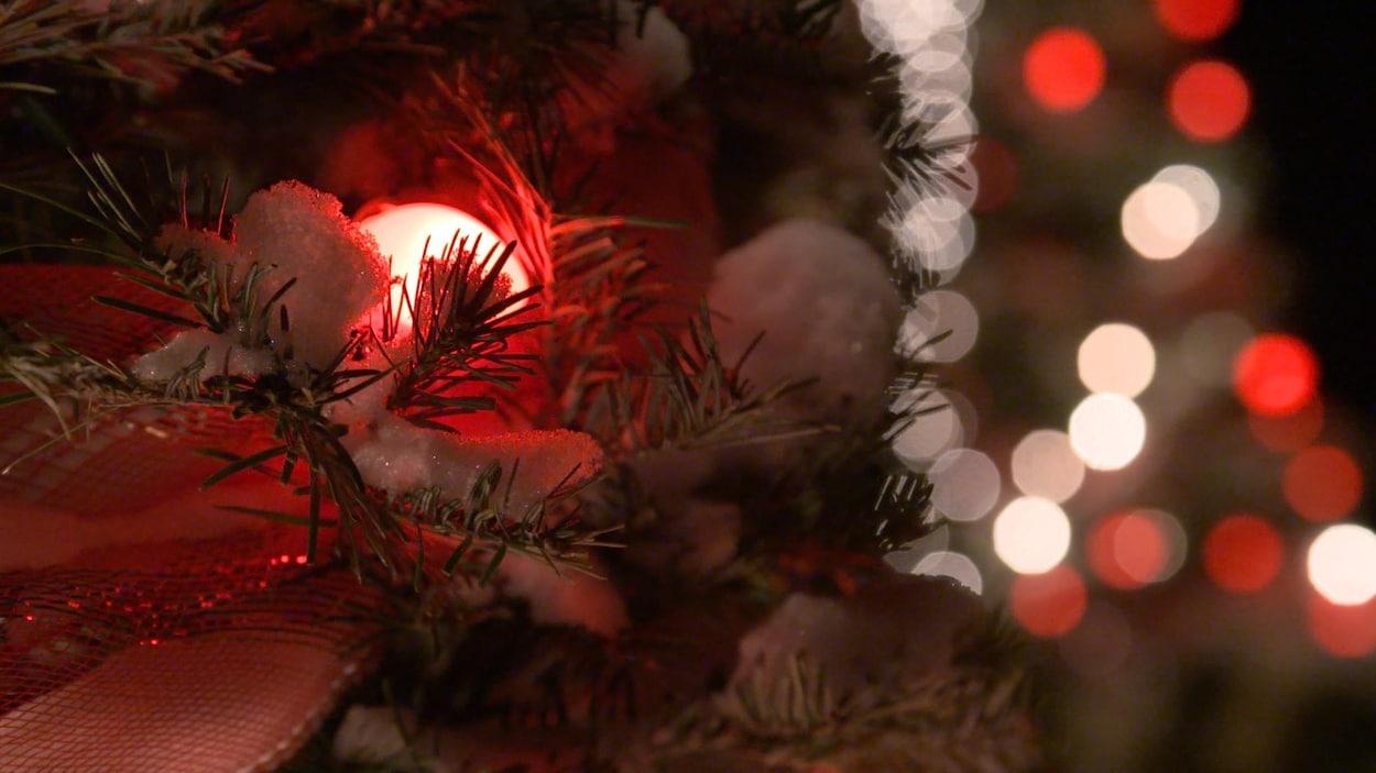 Un sapin à l'extérieur décoré de lumières blanches et rouges.