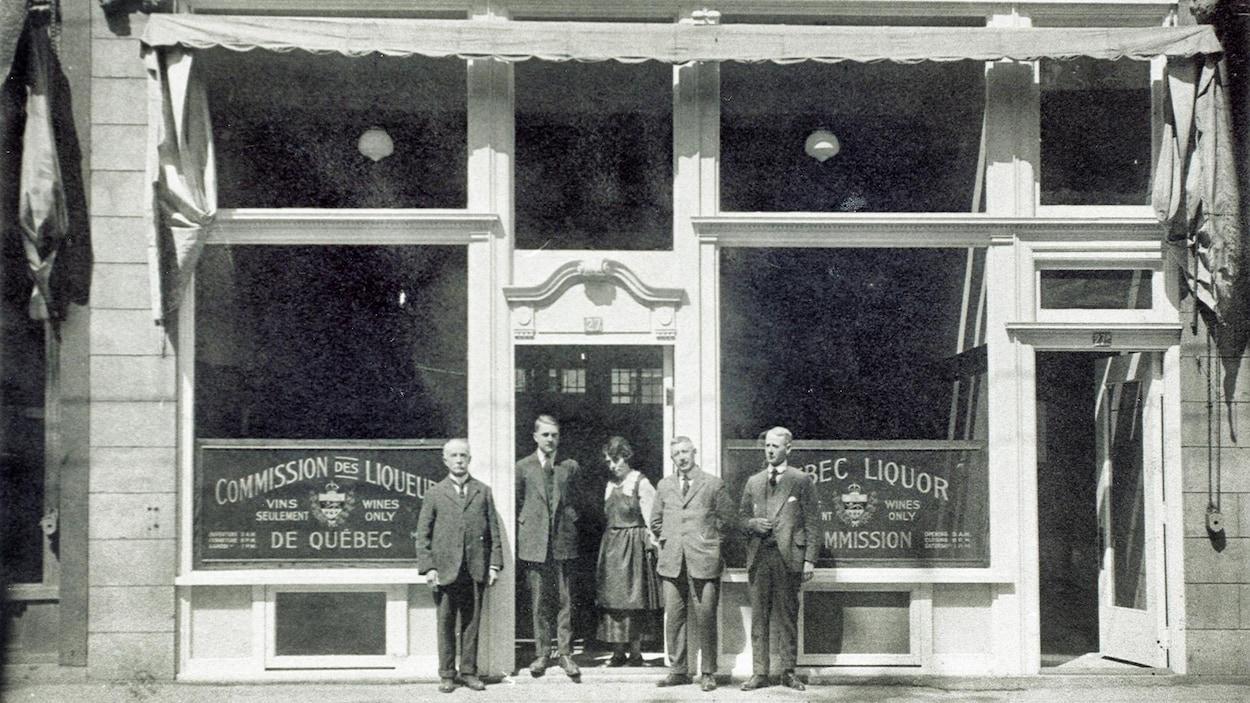 Des gens prennent la pose devant l'un des premiers magasins de la Commission des liqueurs de Québec, durant les années 1920. A l'époque, les produits sont bien cachés derrière des grilles, et ne s'affichent pas en vitrine.