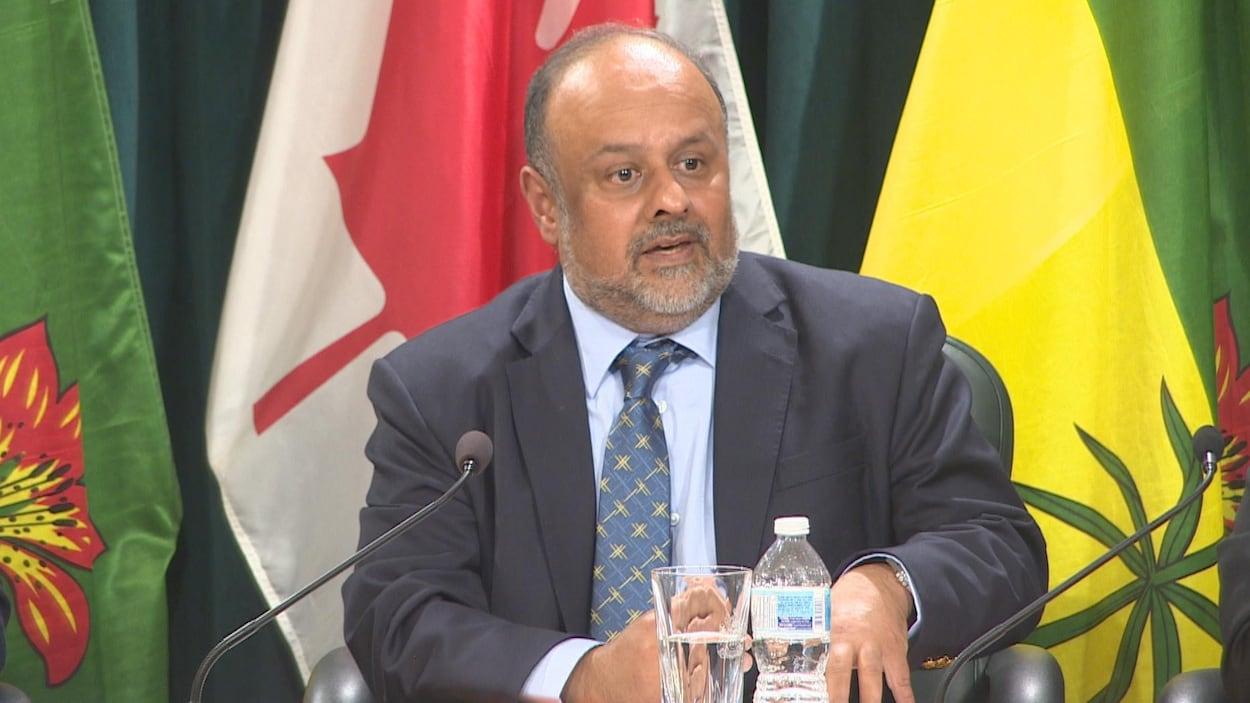 Saqib Shahab assis devant un micro s'adresse aux médias.