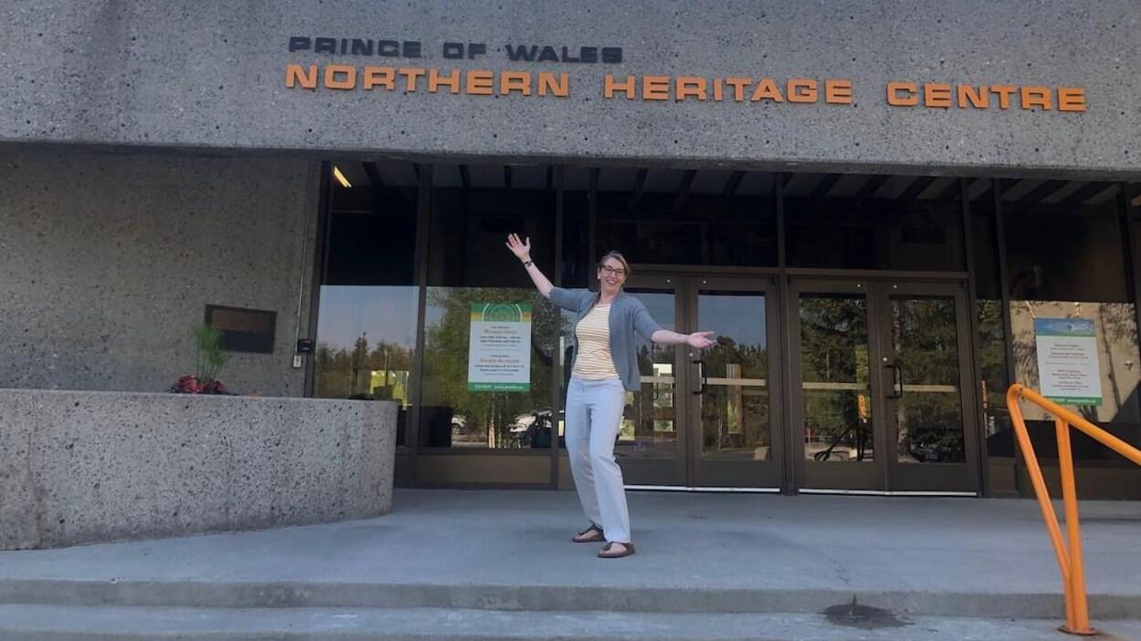La directrice Sara Carr-Locke est debout en souriant devant la porte d'entrée du Centre du patrimoine septentrional