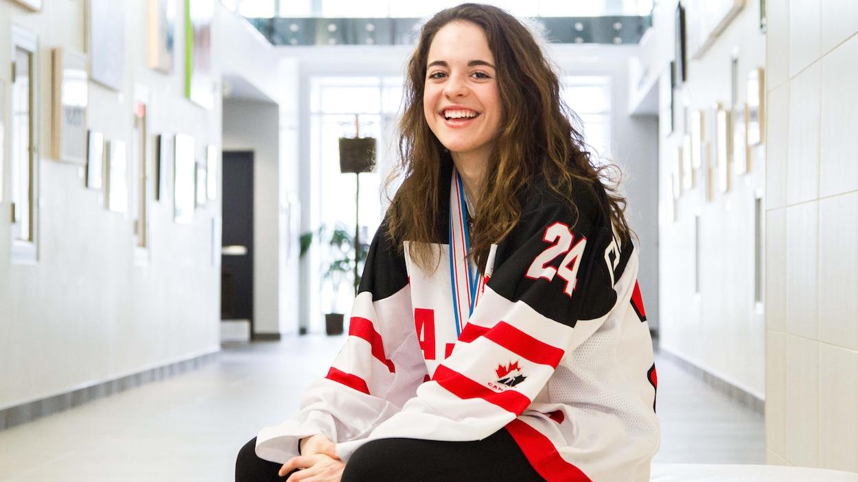 La hockeyeuse Sarah-Ève Coutu-Godbout porte un chandail de hockey et pose dans un grand hall d'entrée.