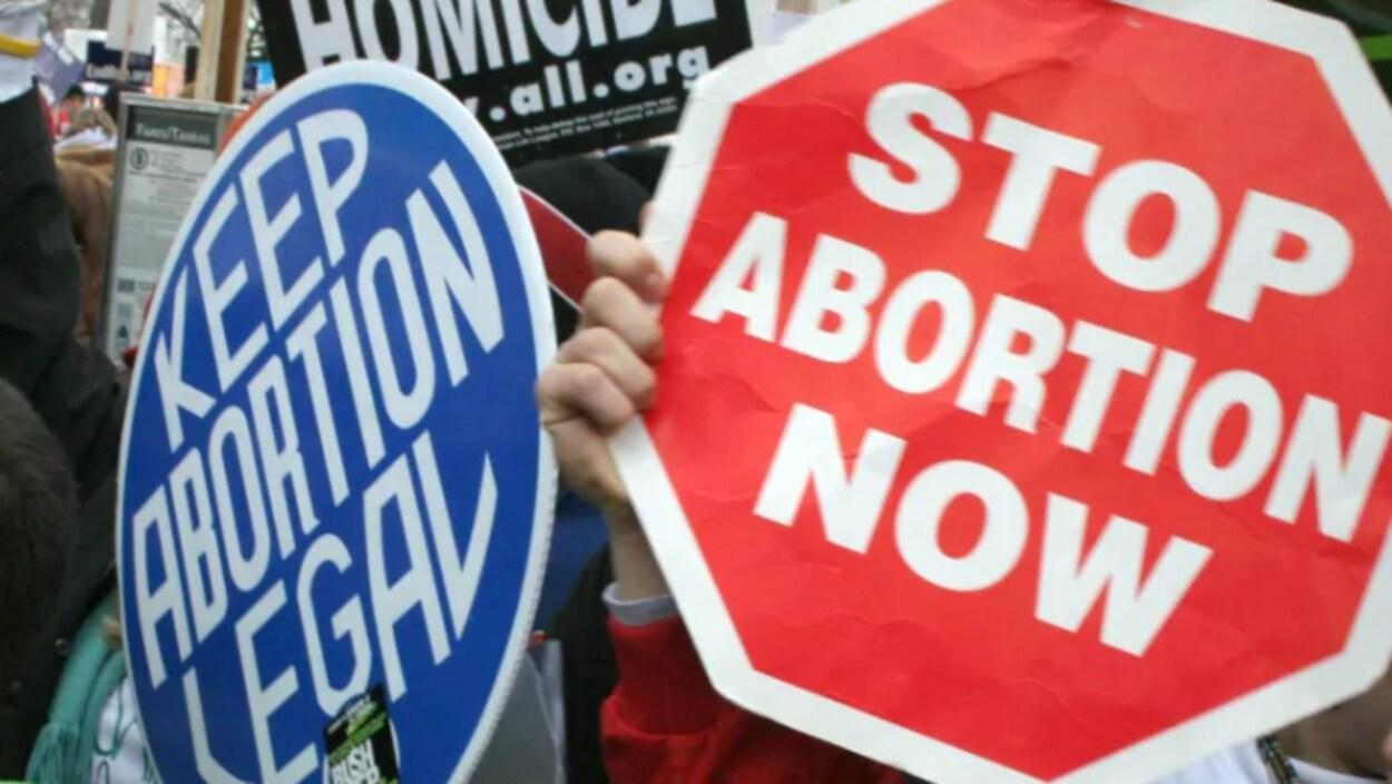 Un panneau bleu indiquant « L'avortement doit rester légal » et l'autre rouge disant « Arrêtez les avortements maintenant ».