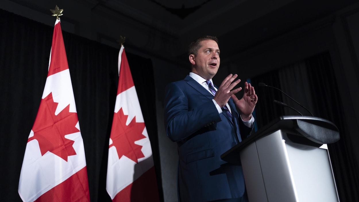 Andrew Scheer fait un discours devant des drapeaux canadiens.