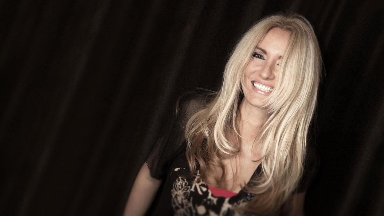 La chanteuse sourit à la caméra durant une séance de photo.