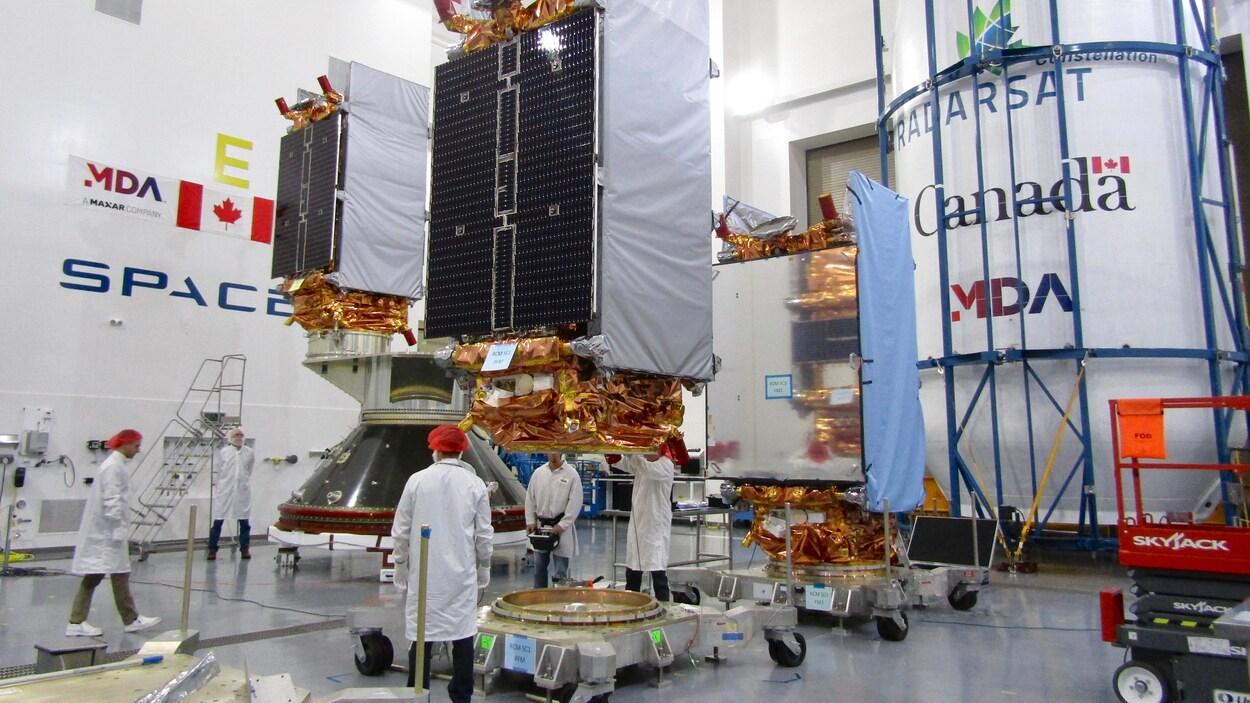 Des ingénieurs préparent les trois satellites de la mission de la Constellation RADARSAT aux à la base aérienne Vandenberg en vue de leur lancement.