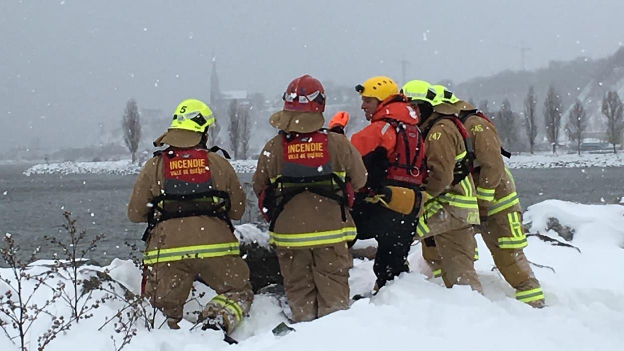 Une équipe d'urgence devant le fleuve Saint-Laurent.