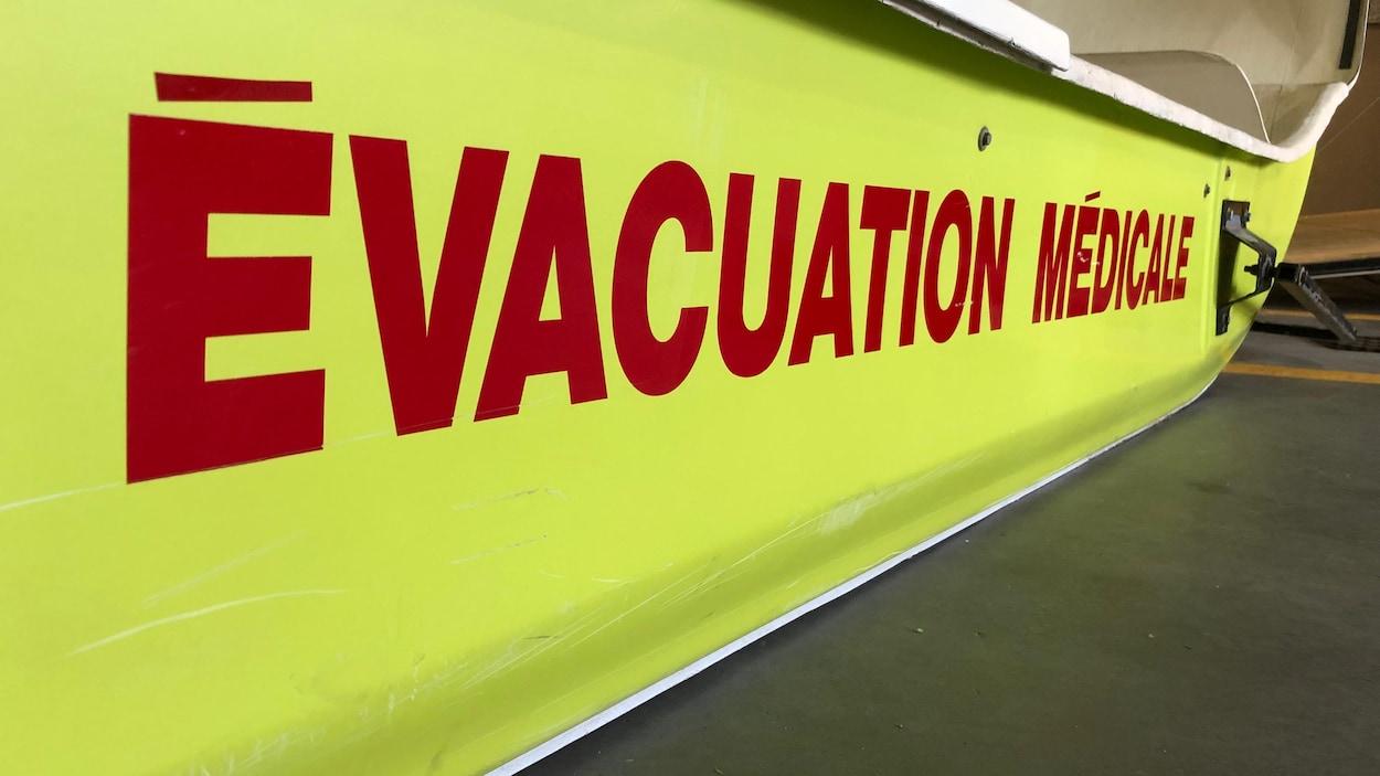 """Un traîneau de sauvetage jaune sur lequel sont inscrits les mots """"évacuation médicale"""" en rouge"""