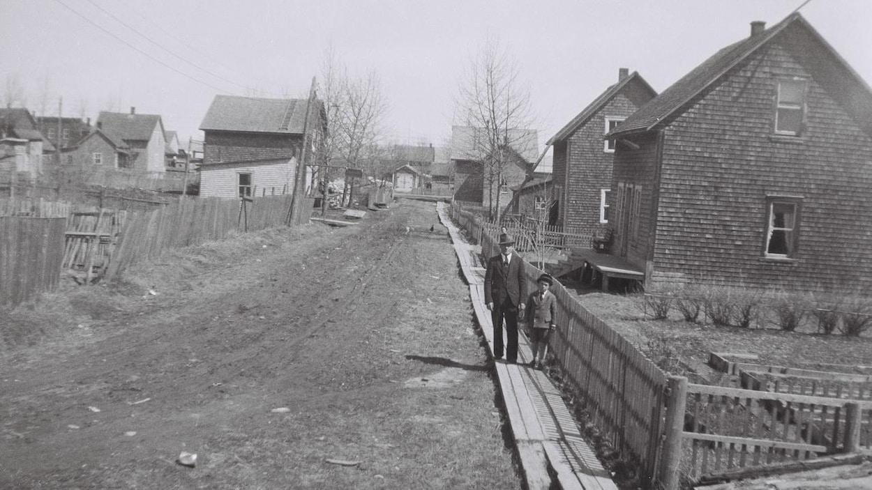 Photo en noir et blanc. Un homme et un enfant se tiennent debout sur un trottoir de bois dans une rue de Sayabec.