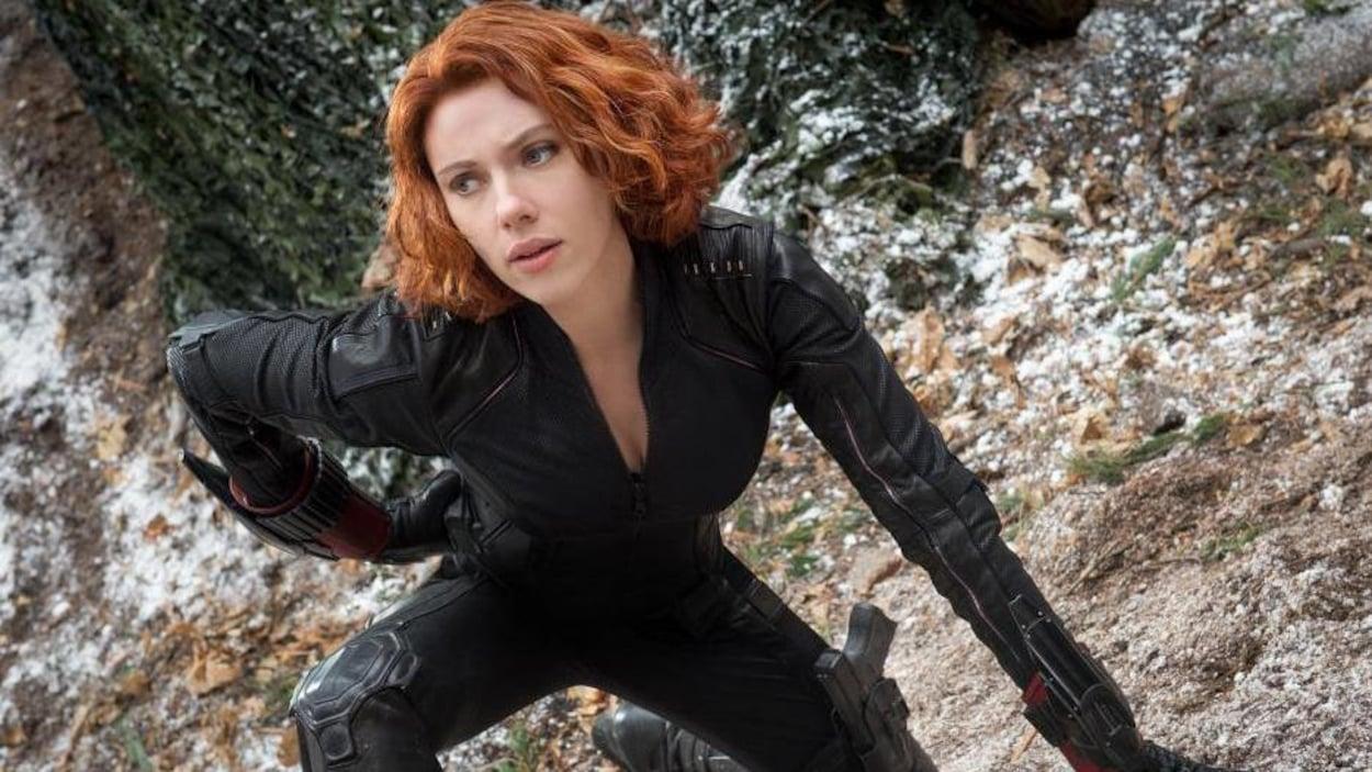 Scarlett Johansson dans le rôle de la Veuve noire est accroupie, un genou à terre, sur un sol rocailleux, dans le film  Avengers: L'ère d'Ultron  (2015).