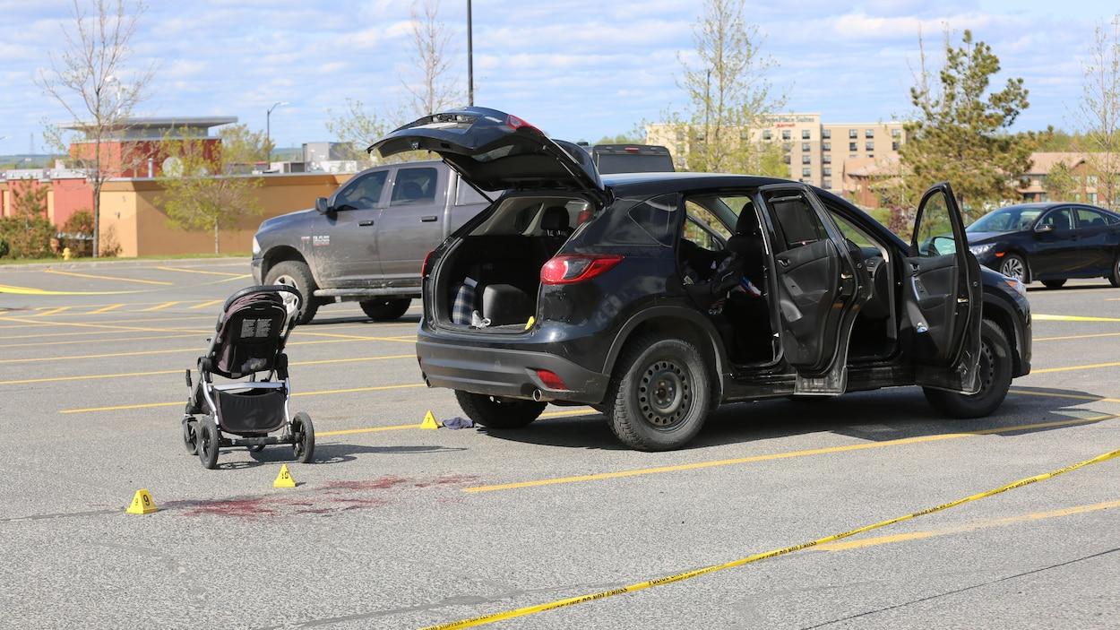 Une voiture et une poussette pour bébés entourés d'un ruban de sécurité de la police.